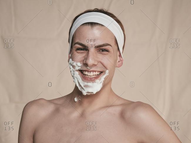 Shirtless androgynous young guy looking at camera while shaving face