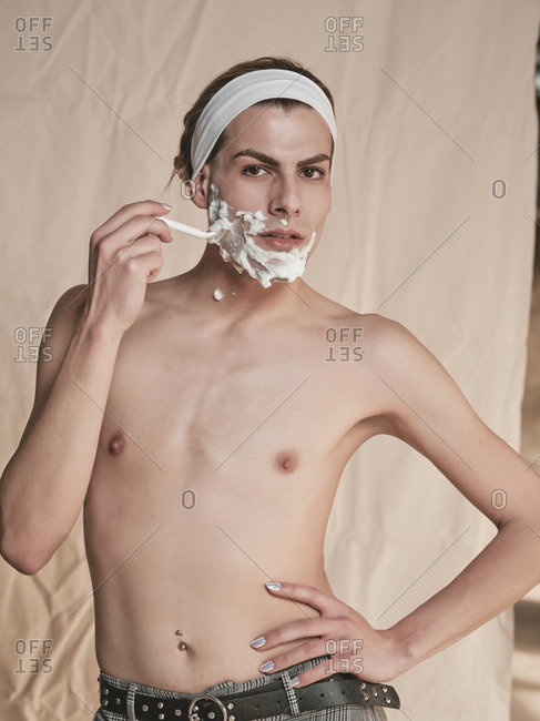Shirtless androgynous young guy with manicure holding hand on waist and looking at camera while shaving face