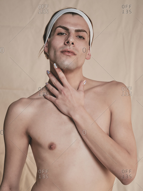 Shirtless androgynous guy with headband looking at camera and touching neck with manicured hand seductively against beige background