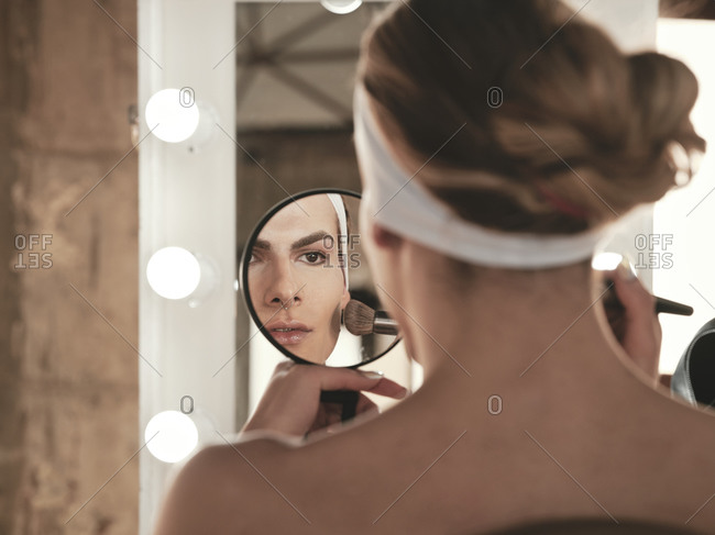 Shirtless androgynous young man with headband applying foundation on cheek while sitting in front of mirror in studio