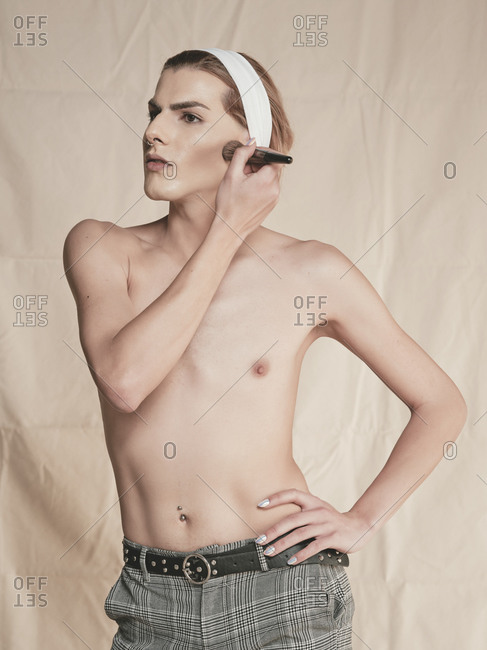 Slim shirtless androgynous man holding hand on waist and looking away while applying rouge on cheek against beige background