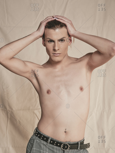 Shirtless androgynous guy looking at camera and touching head with manicured hand seductively against beige background