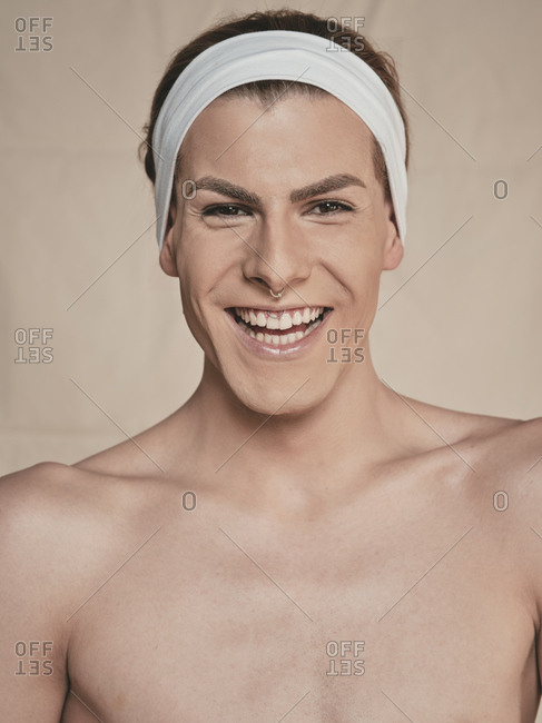 Happy young androgynous male model with makeup and headband looking at camera and laughing against beige background