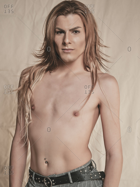 Androgynous young shirtless guy with long hair looking at camera against beige background
