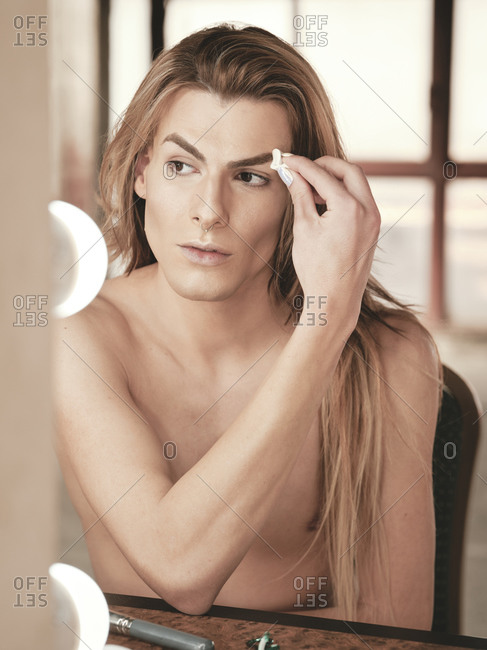 Young androgynous man with long hair applying foundation on face with cotton pad in front of mirror in studio