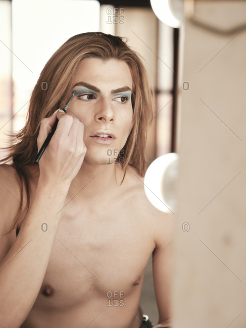 Reflection of young shirtless androgynous man applying eyeshadow near mirror and looking away in studio