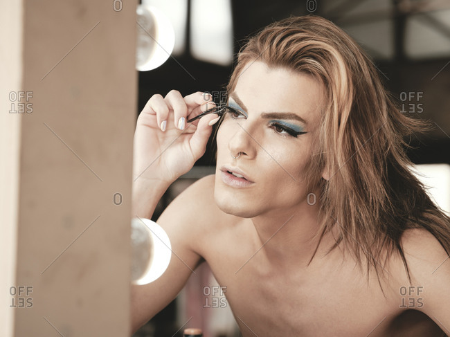 Young androgynous male model with manicure using tweezers to apply fake eyelashes in front of mirror in studio
