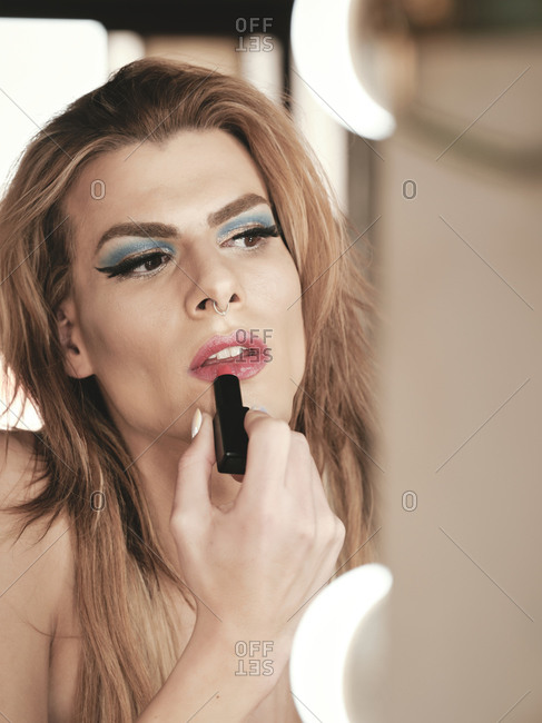 Drag queen with long hair smearing lipstick on lips while applying makeup in front of mirror