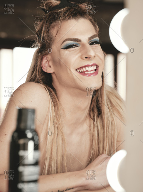 Happy androgynous young guy with stylish makeup and long hair laughing while sitting near mirror in studio