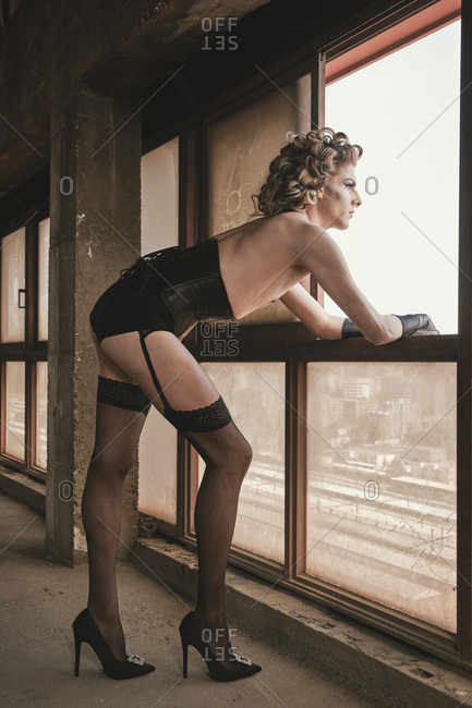 Side view of slim transgender man in corset and high heeled shoes looking out window inside grungy building