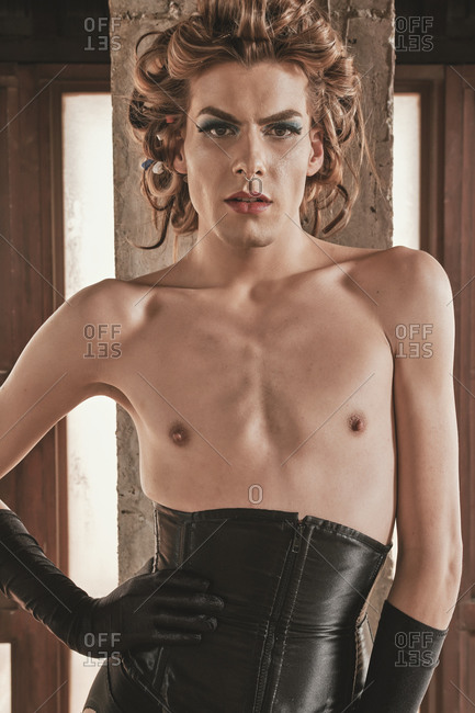 Skinny androgynous male model in kinky corset and elegant black gloves leaning on column against windows