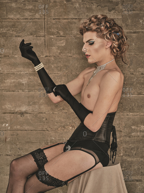 Skinny androgynous male model in kinky corset and elegant black gloves sitting on stool