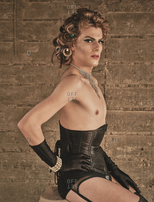 Skinny androgynous male model in kinky corset and elegant black gloves sitting on stool and looking at camera