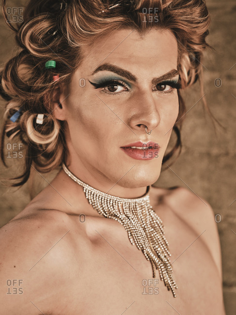 Transgender man with makeup and luxury necklace looking at camera against beige background