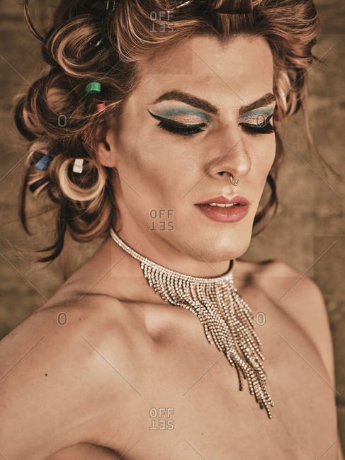 Transgender man with makeup and luxury necklace looking down against beige background