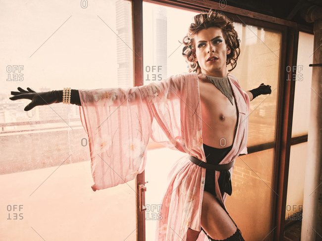 Seductive slim androgynous guy in elegant kinky underwear leaning on glass wall and looking away