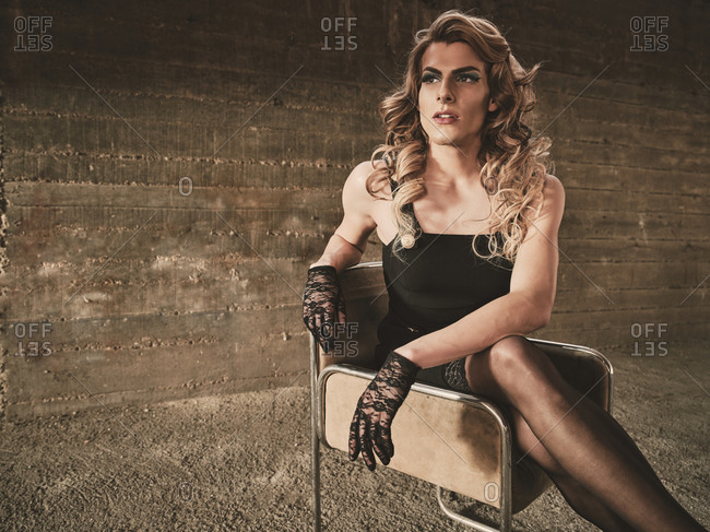Young androgynous guy in elegant feminine clothes looking away while sitting on chair inside grungy building
