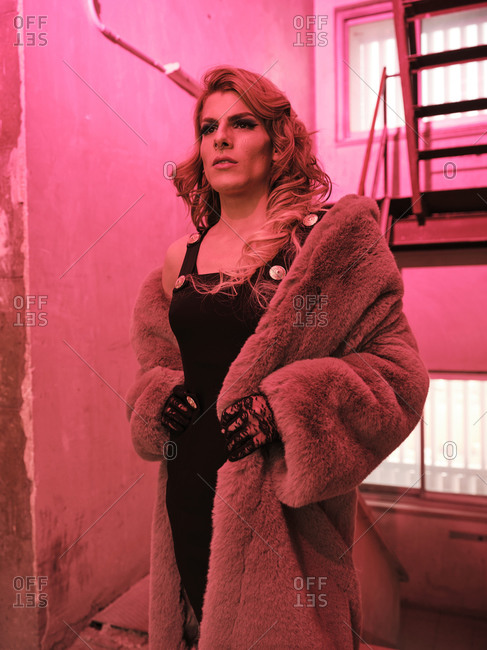 Stylish drag queen in elegant dress and fur coat looking away while standing near staircase under red light inside grungy building