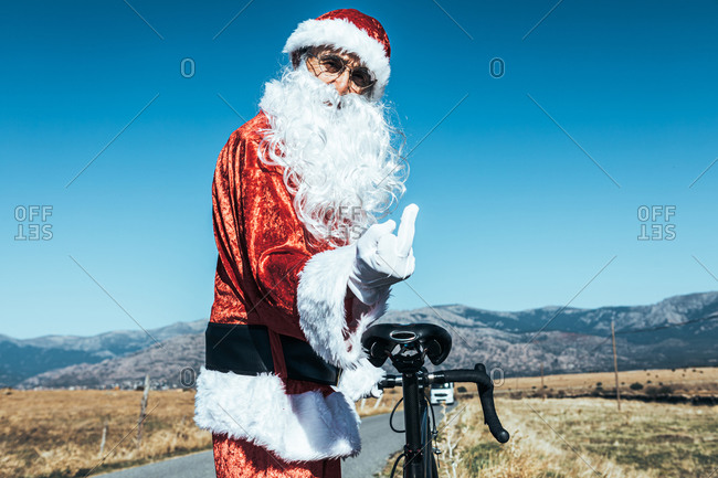 Side view of elderly Santa Claus in costume standing with bicycle on road and showing fuck gesture while looking at camera