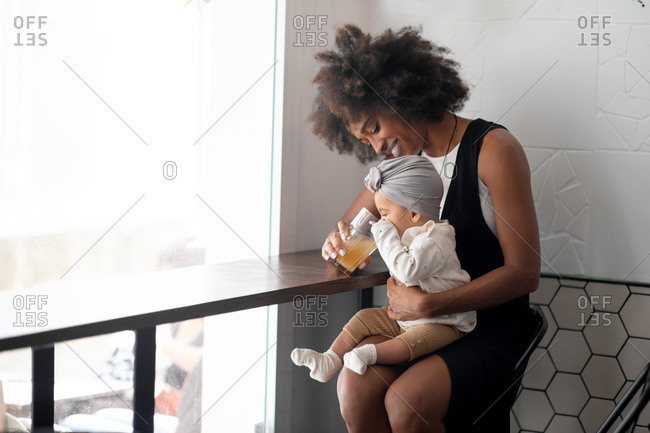 Positive young African America mom feeding little baby with fruit juice while sitting at counter near window at home
