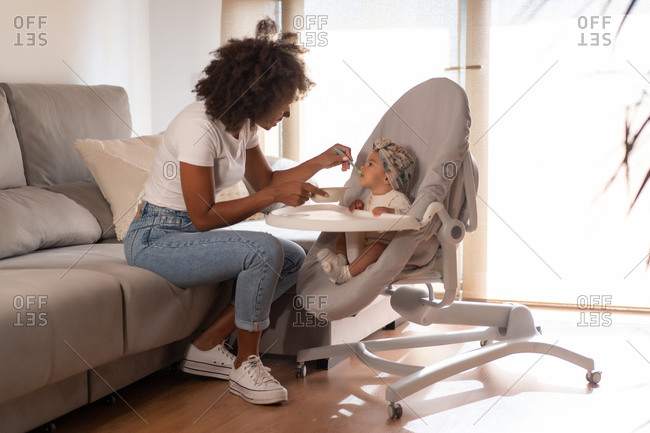 Side view of black woman sitting on sofa and feeding adorable toddler during lunch at home