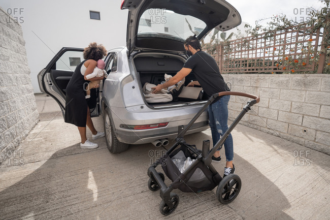 Back view of ethnic man putting luggage and baby stroller in trunk and African American mother with toddler getting in car while preparing for trip