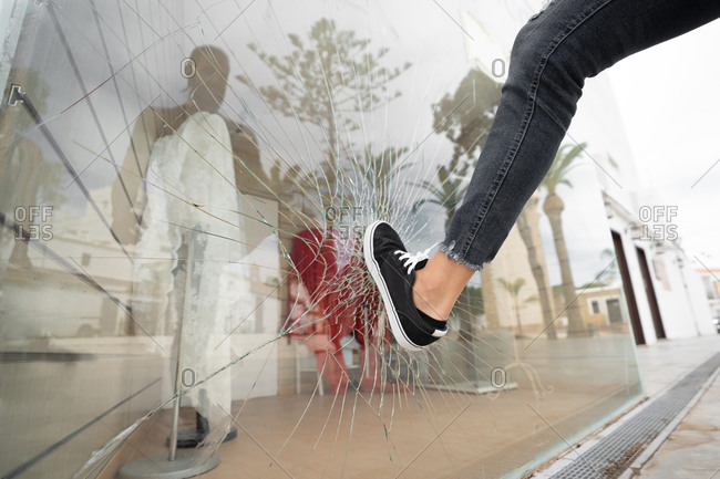 Low angle of crop unrecognizable male vandal breaking showcase of store in city