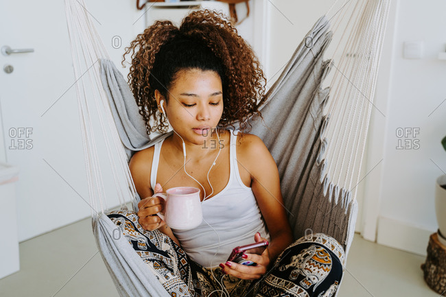 Smiling young African American curly haired female listening to music through earphones while on smartphone while chilling in hammock at home