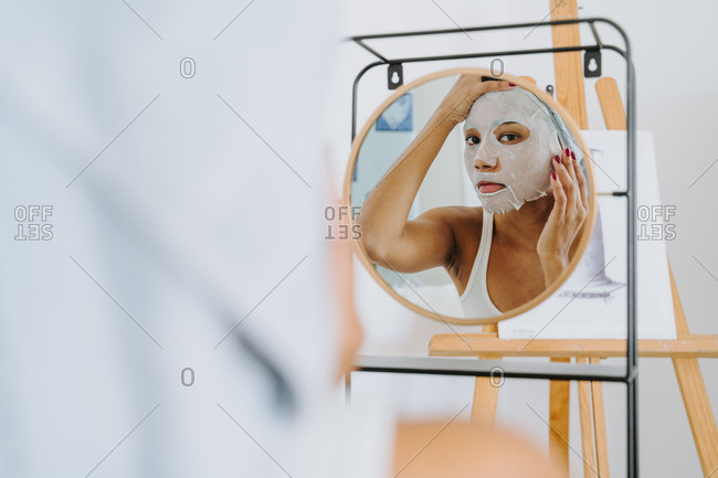Young female reflected in mirror applying skincare moisturizing cloth mask on face during home beauty procedure