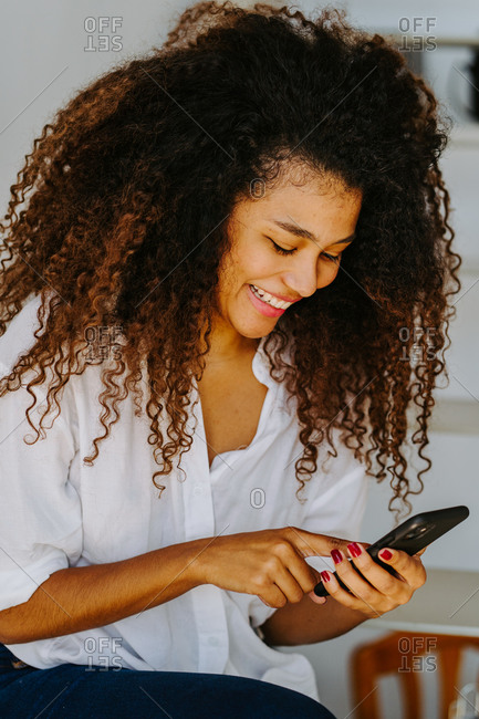 Happy young ethnic curly haired female in casual white blouse and jeans browsing mobile phone while sitting on stairway at home