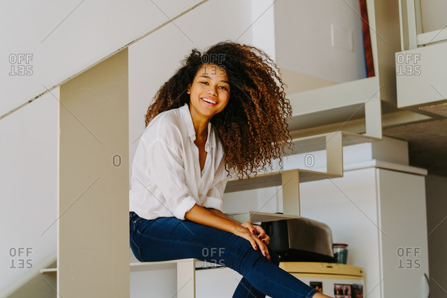 Young cheerful African American female with long curly hair dressed in white blouse and skinny jeans sitting on stairs and looking at camera