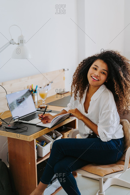 Side view of modern young happy African American female remote employee in casual outfit sitting at table with laptop and writing in planner while working in home office