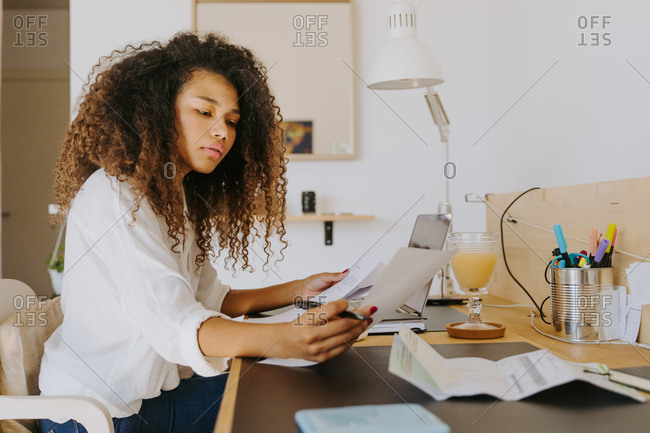 Side view of female bookkeeper sitting at table in home office and analyzing financial reports and paper documents during remote work