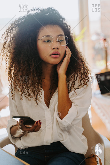 Serious African American female entrepreneur with earbuds sitting at table in home office and reading messages on cellphone during distant work