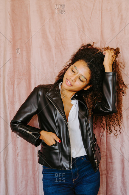 Young African American female with curly hair wearing trendy leather jacket touching hair and standing on pink background