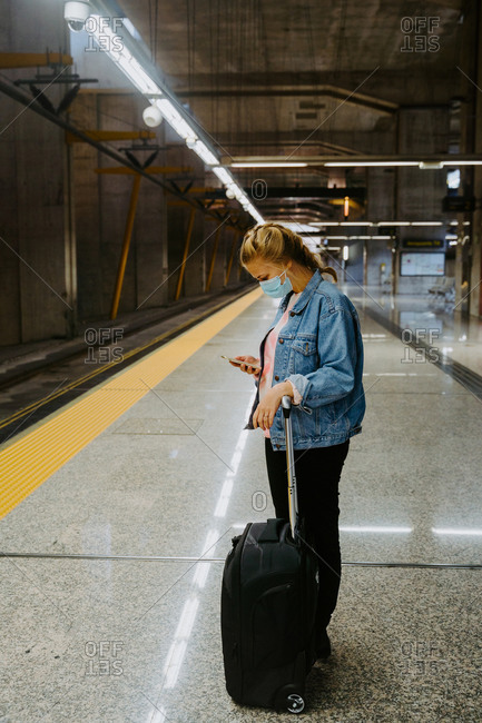 Side view of female texting on cellphone while waiting for arriving train in station