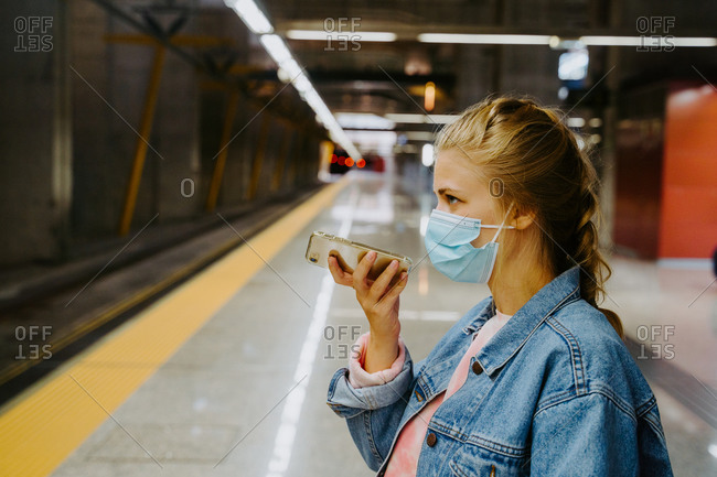 Side view of female recording voice message on cellphone while waiting for arriving train in station