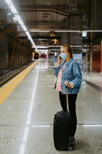 Side view of female speaking on cellphone while waiting for arriving train in station looking away