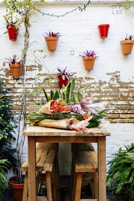 Wooden table at floristry workshop full of flowers for arrangements