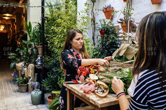 Professional female florists arranging flower bouquet while working together in shop sitting on wooden table