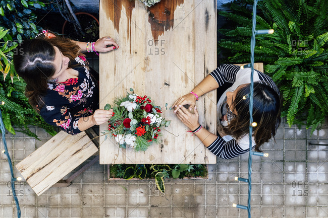 From above professional female florists arranging flower bouquet while working together in shop sitting on wooden table