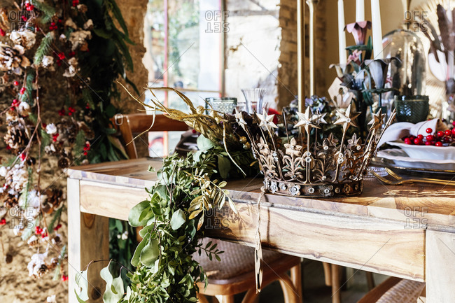 Decorative vintage crown and leaves on wooden table in decor shop during Christmas season