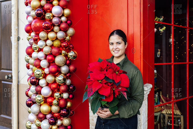 Woman standing outside shop red door with christmas decorative baubles holding pot of poinsettia flower in daylight looking at camera