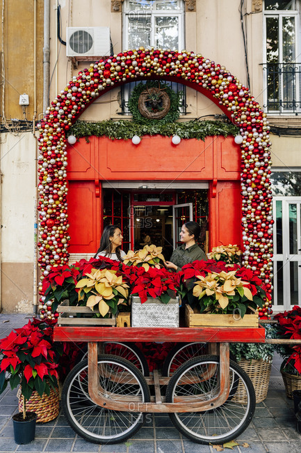 Woman standing outside shop with female costumer at red door with christmas decorative baubles holding pot of poinsettia flower in daylight