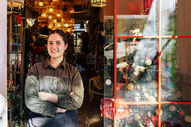 Woman standing outside shop with christmas decorative baubles and garlands in daylight
