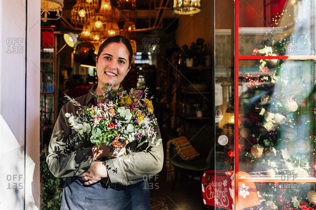 Woman holding flower bouquet standing outside shop with christmas decorative baubles and garlands in daylight looking at camera