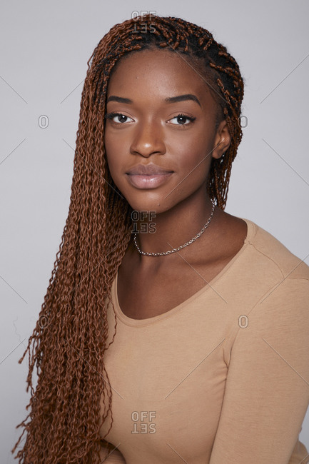 Relaxed African American female in casual outfit and with braids sitting on gray background in studio and tenderly looking at camera