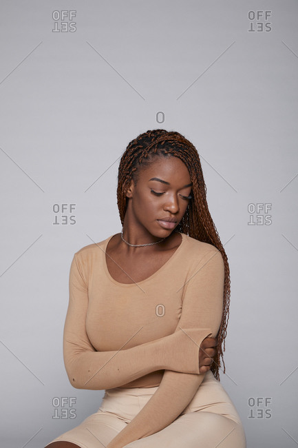 Relaxed African American female in casual outfit and with braids sitting on gray background in studio and tenderly looking down