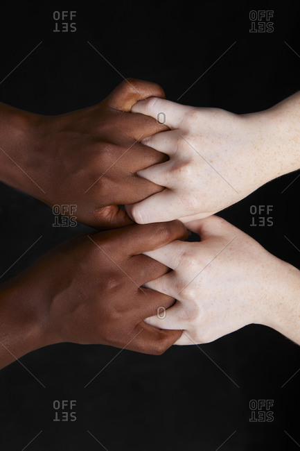 Top view of crop anonymous multiracial females tightly holding hands on black background in studio demonstrating concept of racial equality