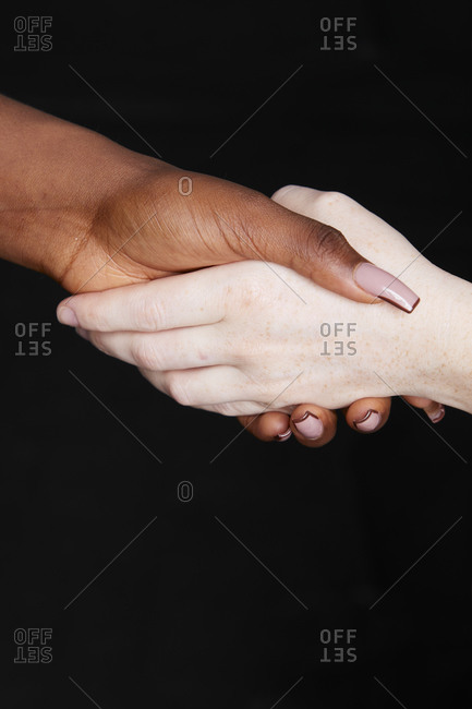 Crop unrecognizable multiethnic females holding and shaking hands as greeting and equal gesture on gray background in studio